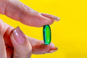 Nahaufnahme Schmerzmedikament in Kapselform in Frauenhand vor gelbem Hintergrund