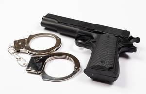 Nahaufnahme schwarze Waffe neben Handschellen isoliert vor weißem Hintergrund