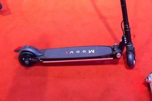 Nahaufnahme Stehfläche von klappbarem E-Scooter von Moovi auf rotem Teppich