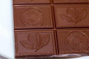 Nahaufnahme Tafel heller Schokolade mit verschiedenen Motiven auf einzelnen Schokoladenstücken