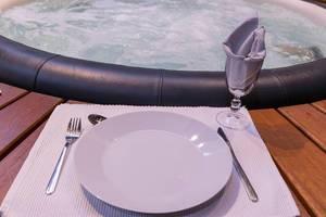 Nahaufnahme Tischgedeck mit Teller, Besteck und Glas auf Ablage vor Whirlpool