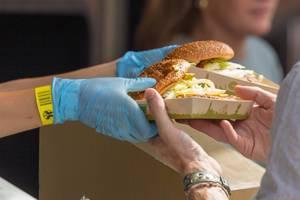 Nahaufnahme Verkäufer übergibt zwei Pappteller mit Hamburger an Kunden