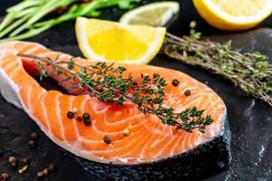 Nahaufnahme vom Lachsfleisch mit frischem Thymian und Pfefferkörner, neben Zitronenscheiben auf schwarzem Untergrund