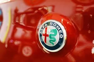 Nahaufnahme von Alfa Romeo Logo auf rotem Hintergrund