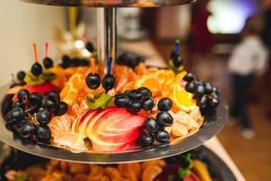Nahaufnahme von Äpfeln, schwarzen Trauben, Mandarinen und Orangen