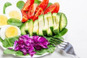 Nahaufnahme von Avocadoscheiben neben Rotkraut, mit Spinat Tomaten und hartgekochten Eiern