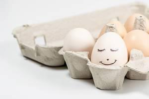 Nahaufnahme von bemaltem Ei mit lächelndem Gesicht im Karton mit mehreren Eiern
