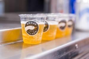Nahaufnahme von Bier in kleinen Plastikbechern mit dem Goose Island Logo mit Gans und Schriftzug