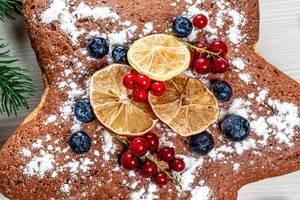 Nahaufnahme von Biskuitkuchen mit Beeren, Puderzucker und getrockneten Zitrusfrüchten