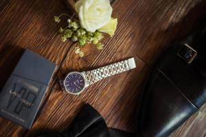 Nahaufnahme von Bräutigam-Accessoires wie Blumengesteck, Uhr und schwarze Schuhe auf Holztisch