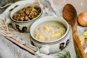 Nahaufnahme von Brei aus Perlgerste mit Fleisch und Gemüse neben Holzlöffel und ganzer Zwiebel