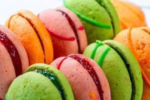 Nahaufnahme von bunten, gefüllten Macarons vor weißem Hintergrund