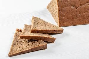 Nahaufnahme von dreieckig geformten Brotscheiben eines Roggenbrotes auf weißem Holztisch