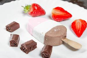 Nahaufnahme von einem Eis mit Schokoladenwürfeln und Erdbeeren auf weißem Teller
