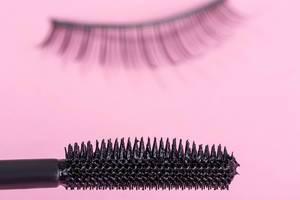 Nahaufnahme von einem Mascara-Bürsten auf pinkem Hintergrund mit künstlichen Wimpern