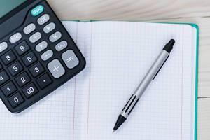 Nahaufnahme von einem Notizheft mit Taschenrechner und Stift