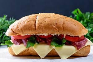 Nahaufnahme von einem Sandwich-Baguette mit Salami, Tomatenscheiben, Käse und grünen Kräutern