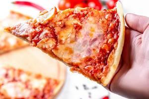 Nahaufnahme von einem Stück Pizza in der Hand
