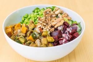 Nahaufnahme von einem veganes Bowls mit gegrilltem Gemüse, Walnüsse, Reis, Edamame und Soja-Sesam Dressing auf einem Holztisch