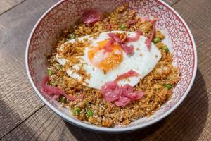 Nahaufnahme von einem vegetarischen Gericht mit gebratener Reis, Erbsen, Karotten, Zwiebeln, Chili, Knoblauch und Spiegelei