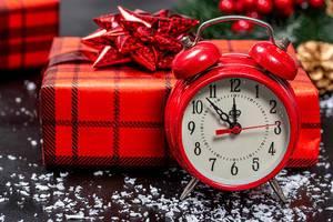 Nahaufnahme von einem Weihnachtsgeschenk in roter Verpackung mit einem roten Wecker im Vordergrund