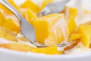 Nahaufnahme von einer Gabel mit Mangostück im griechischen Joghurt