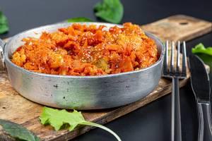 Nahaufnahme von einer Metallpfanne mit gedämpftem Fisch und Gemüse in Tomatensauce auf einem Schneidebrett mit Kräuterblättern, Messer und Gabel vor schwarzem Hintergrund