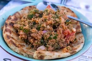 Nahaufnahme von Fladennbrot mit Quinoa-Tamboule mit aromatischen Tomaten aus Paros, Griechenland