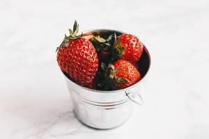 Nahaufnahme von frisch gepflückten Erdbeeren in kleinem Blecheimer