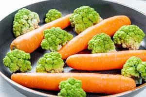 Nahaufnahme von frischen Karotten und Brokkoli in einer Bratpfanne auf einem Holztisch