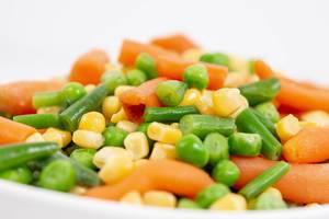 Nahaufnahme von frischen Möhren, Mais, grünen Bohnen und Erbsen in einer weißen Schüssel