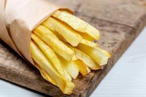 Nahaufnahme von frischen Pommes in einer Papiertüte auf einem Holzbrett