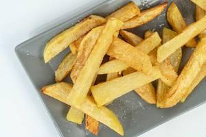 Nahaufnahme von frittierten und gesalzenen Pommes auf einem grauen Teller auf weißem Hintergrund