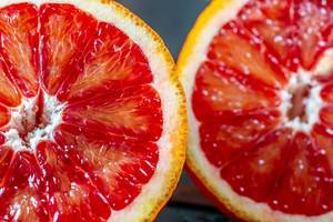 Nahaufnahme von Fruchtfleisch zweier saftiger Blutorangen-Hälften vor dunklem Hintergrund