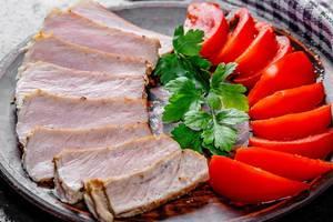 Nahaufnahme von gebackenem Fleisch, in Scheiben geschnitten und Tomatenscheiben, auf einem runden Tablett angerichtet, mit frischen Kräutern