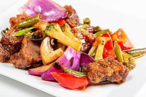 Nahaufnahme von gebratenem Rindfleisch mit buntem Gemüse und Pilzen