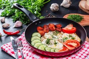 Nahaufnahme von gebratenen Spiegeleiern mit Gurken, Tomaten, Wurstsxhceiben und Kräutern