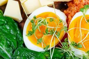 Nahaufnahme von gekochtem Ei in die Hälfte geschnitten, mit frischem Gemüse zum Frühstück serviert