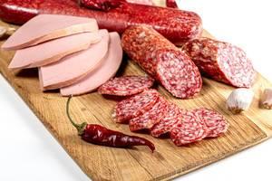 Nahaufnahme von geräucherter Salami und anderen Wurstwaren auf einem Küchenbrettchen aus Holz
