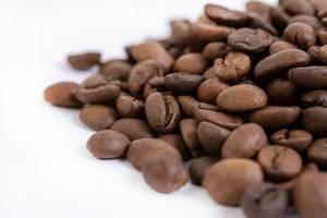 Nahaufnahme von gerösteten Kaffeebohnen auf weißem Tisch