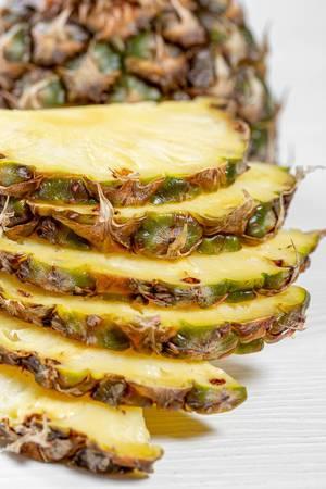 Nahaufnahme von geschnittenen Ananas Scheiben gestapelt auf weißem Holztisch