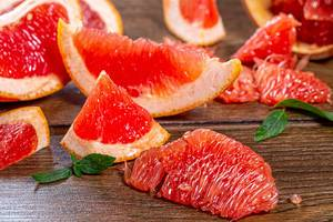 Nahaufnahme von geschnittener Grapefruit auf einem braunen Holztisch
