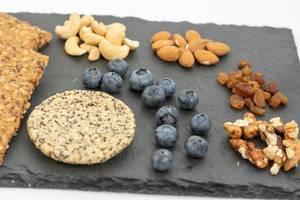 Nahaufnahme von gesunden Alternativen für Süßigkeiten, wie Blaubeeren, Mandeln, Rosinen, Walnüsse und Knäckebrot