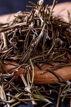 Nahaufnahme von getrockneten Kräutern (Rosmarin) auf Holz