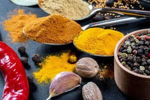 Nahaufnahme von Gewürzpulvern auf Löffeln - Kurkuma, Curry und Knoblauch mit Muskatnuss, Piment und einer roten Chilischote neben buntem Pfeffer