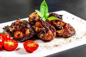 Nahaufnahme von glänzenden Hähnchenstücken, gebraten und serviert mit Cherry-Tomaten und Basilikum