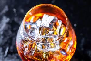 Nahaufnahme von Glas mit Eiswürfeln und Cognac vor dunklem Hintergrund