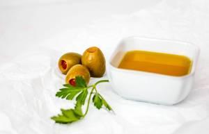 Nahaufnahme von grünen Oliven und Olivenöl