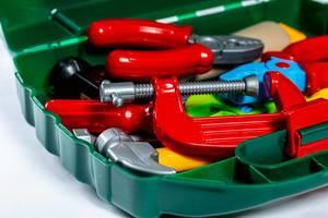 Nahaufnahme von Handwerk-Spielzeug in Werkzeugkiste vor weißem Hintergrund