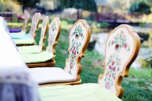 Nahaufnahme von hölzernen Stühlen mit traditionellem Muster im Garten